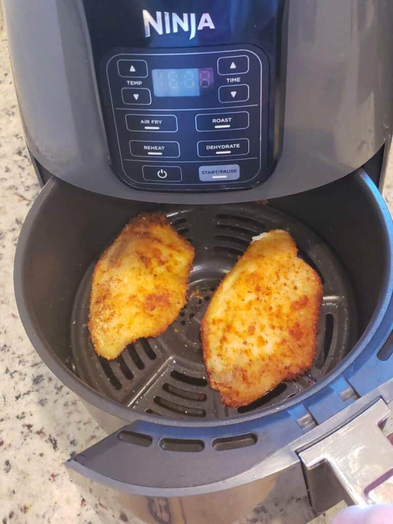 2 air fried tilapia fillets in air fryer basket