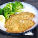 breaded tilapia on blue and white plate with broccoli and lemon