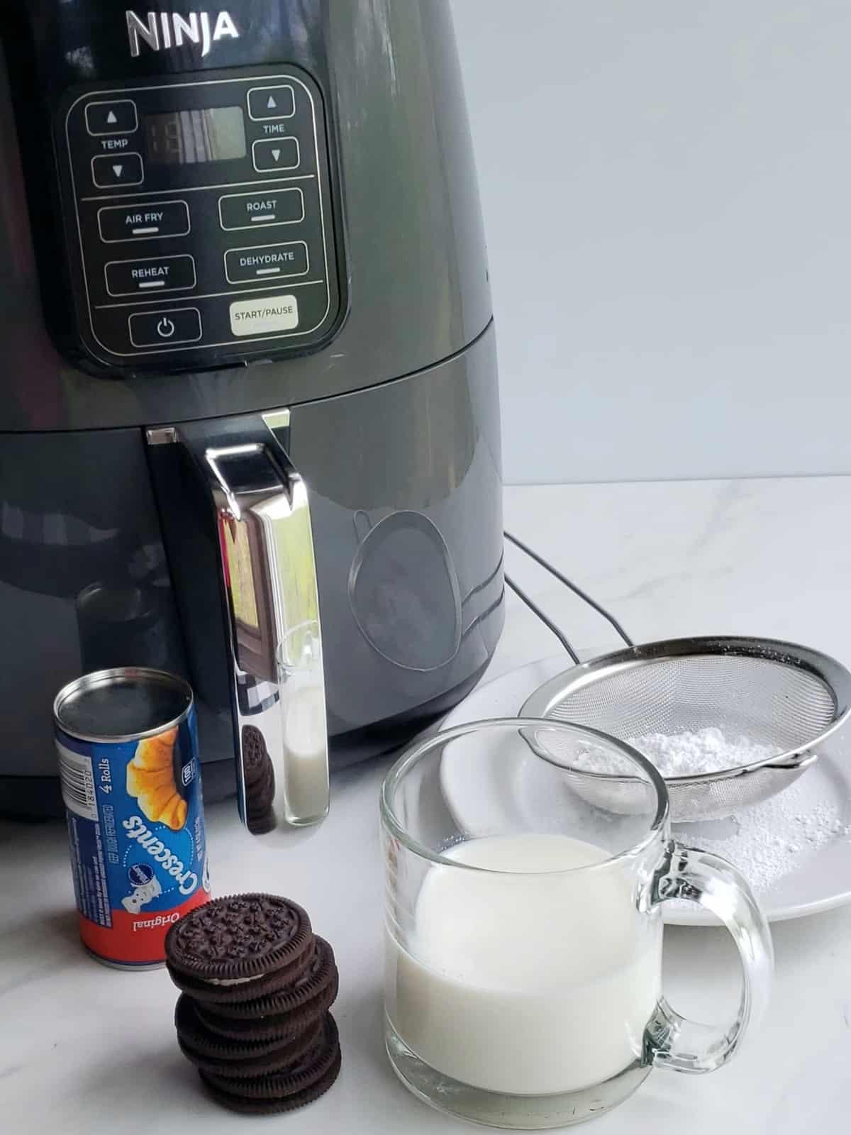 air fryer. stack of chocolate creme filled cookies cup of milk. sieve of powdered sugar