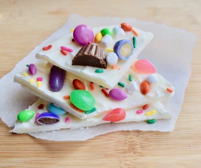 Three stacked pieces of white chocolate bark with Easter candy pressed into them placed on parchment paper