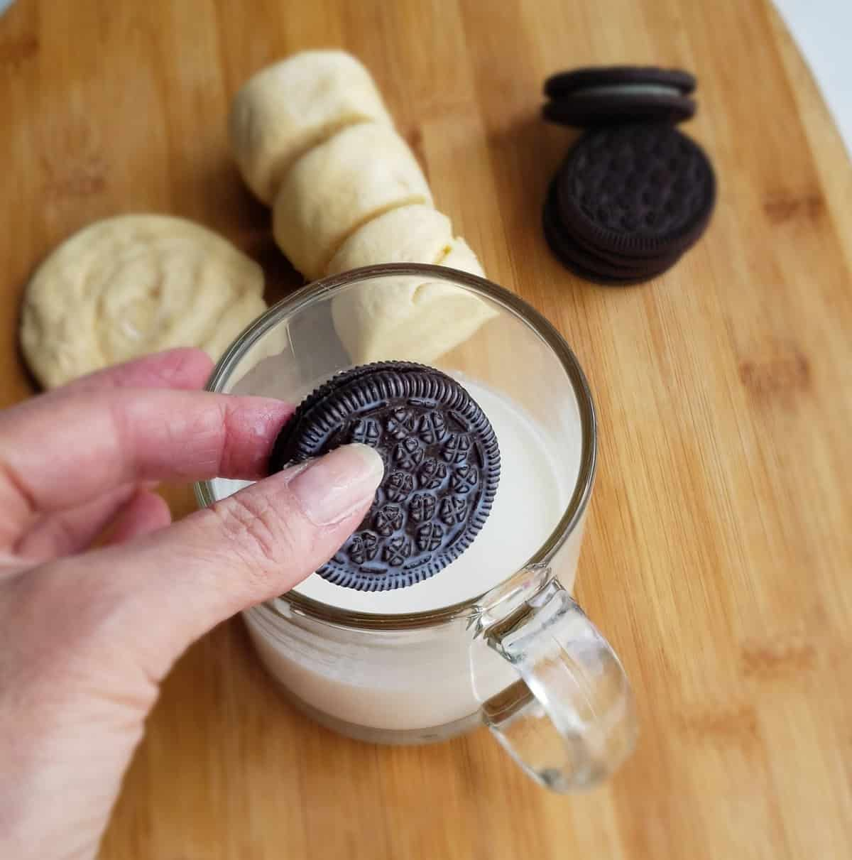 hand dipping chocolate cookie in glass cup of milk