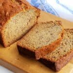 banana bread sliced on wooden cutting board with blue and white cloth