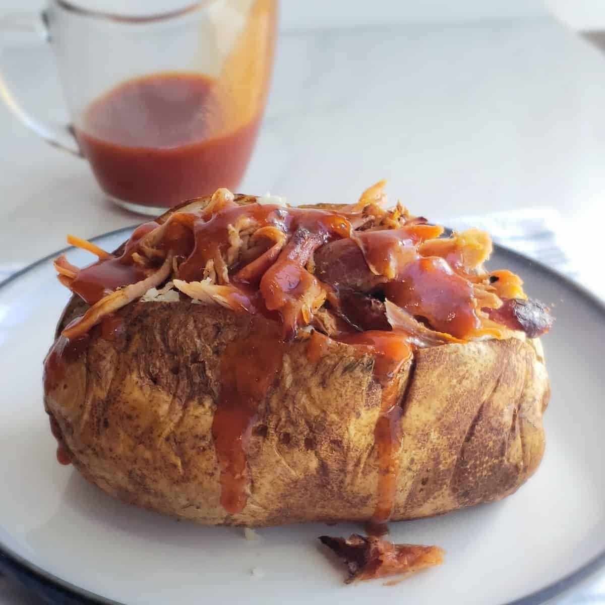 Baked potato stuffed with meat covered in sauce on a white plate. A clear tiny pitcher of bbq sauce in background with sauce dripping down the side