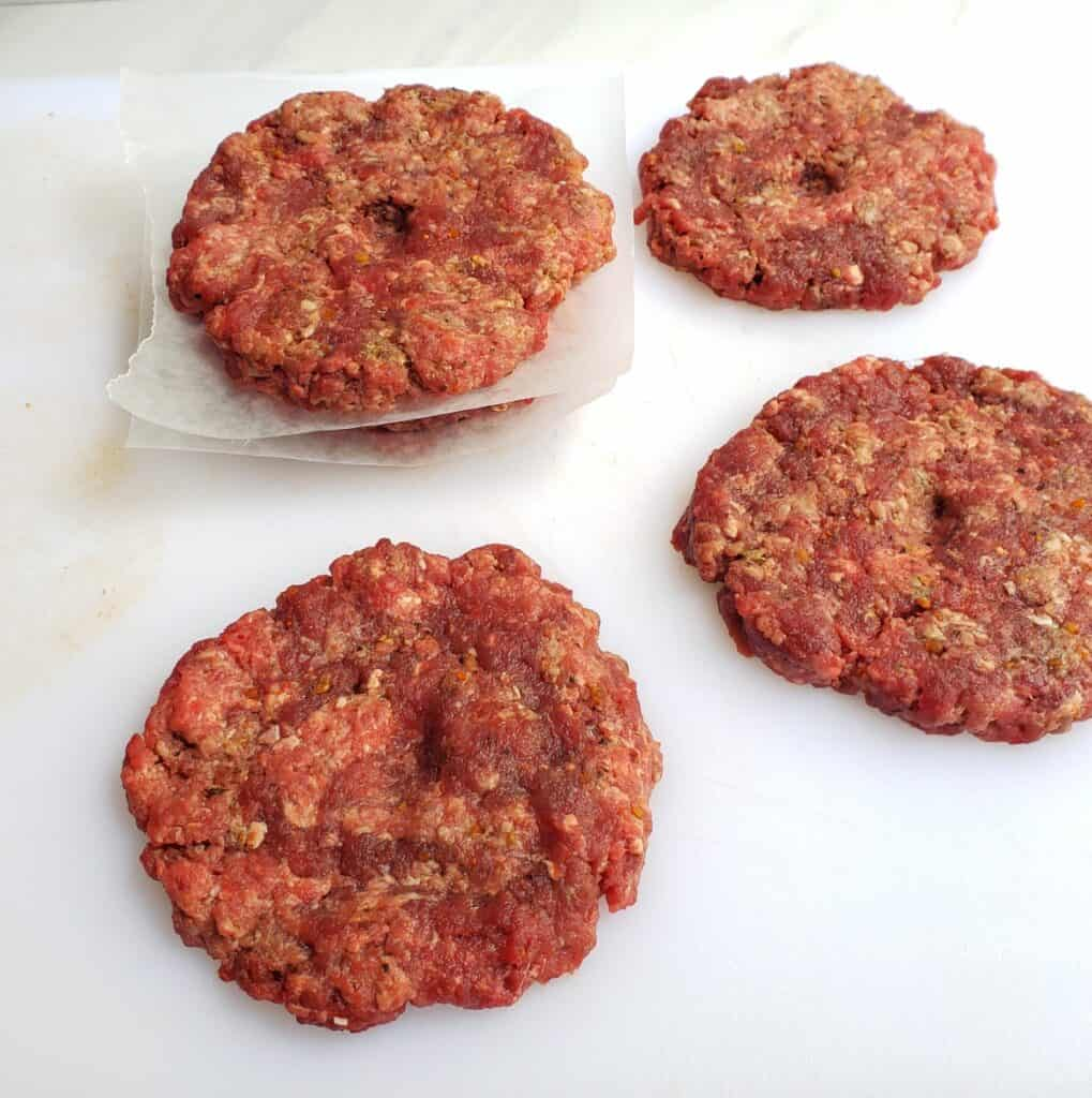 ground meat patties stacked between wax paper. some on white surface