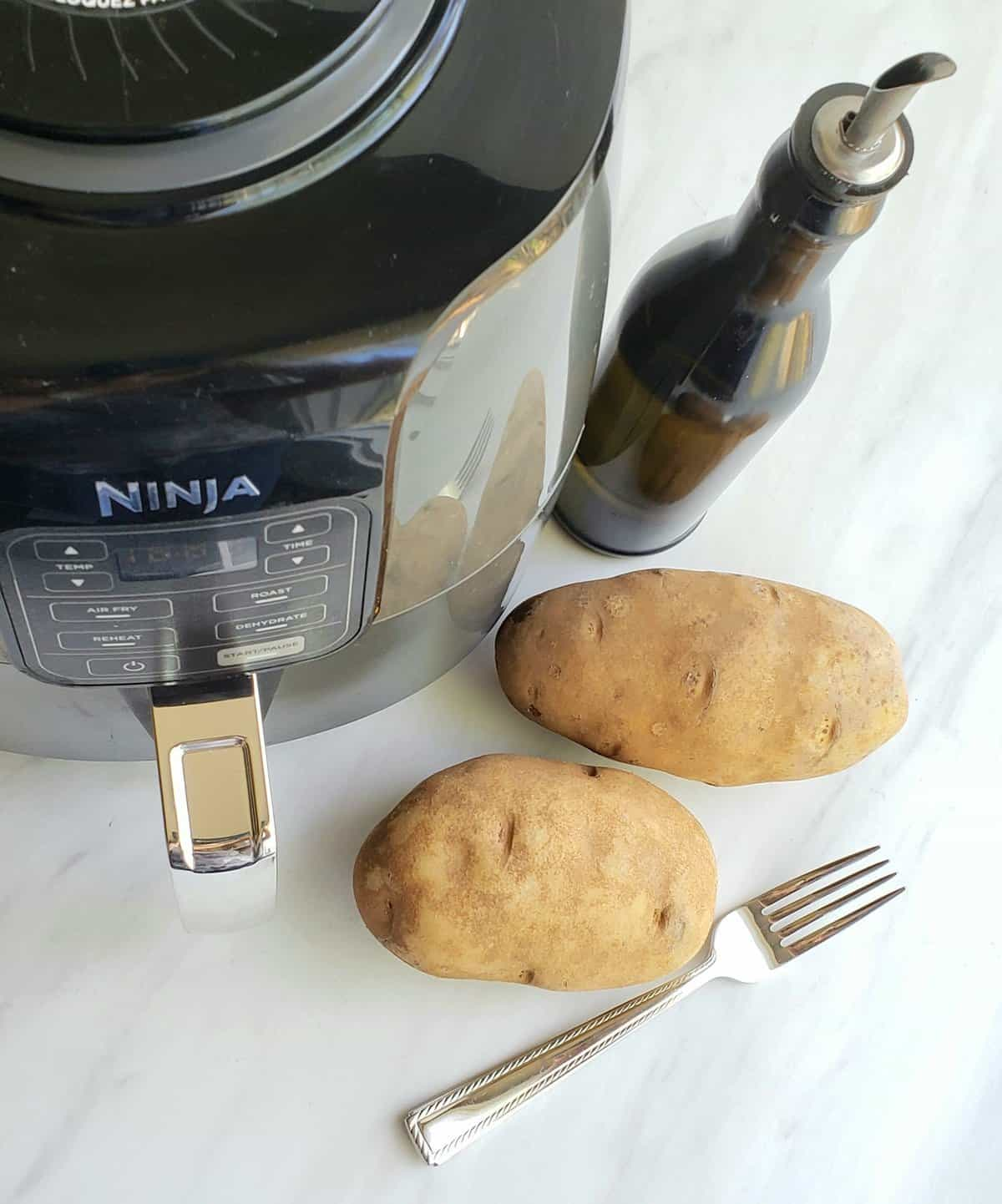 Air fryer, 2 baking potatoes, a fork and an oil dispenser on a white surface