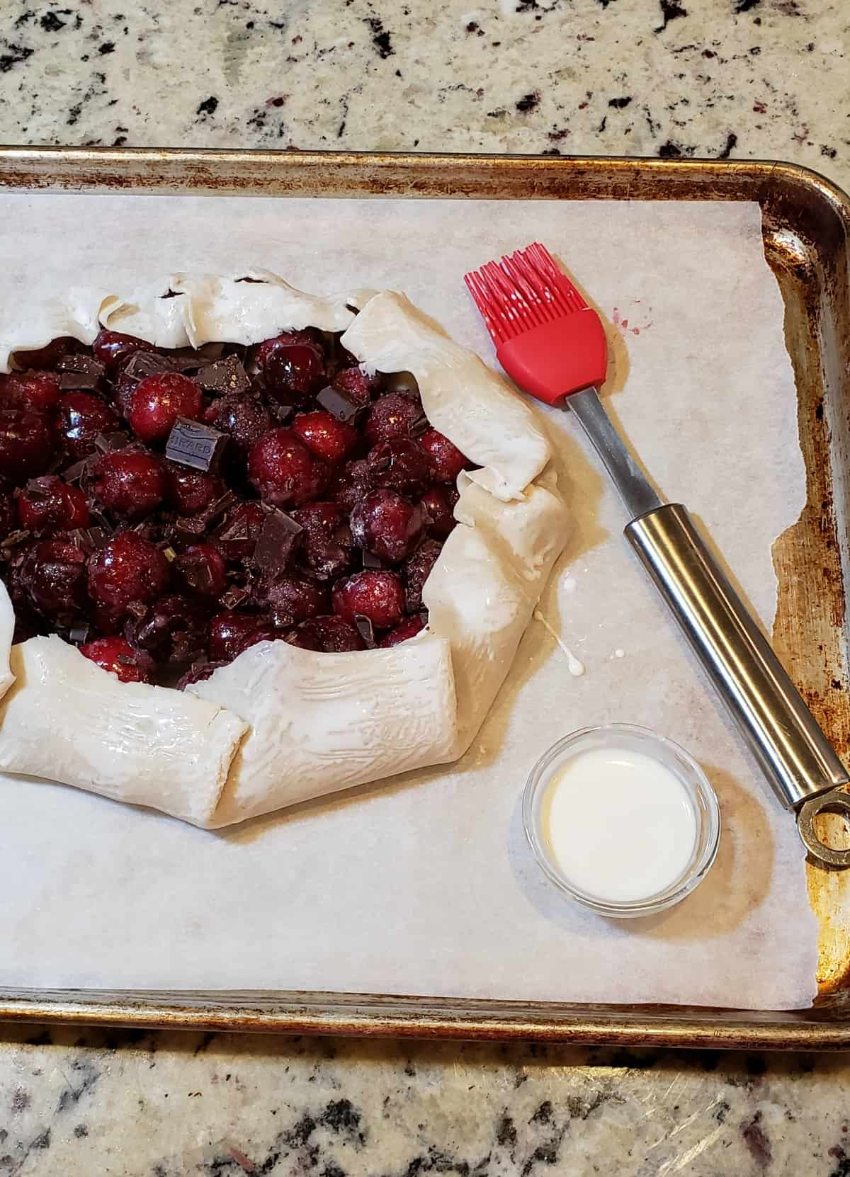 uncooked cherry galette on parchment with red pastry brush