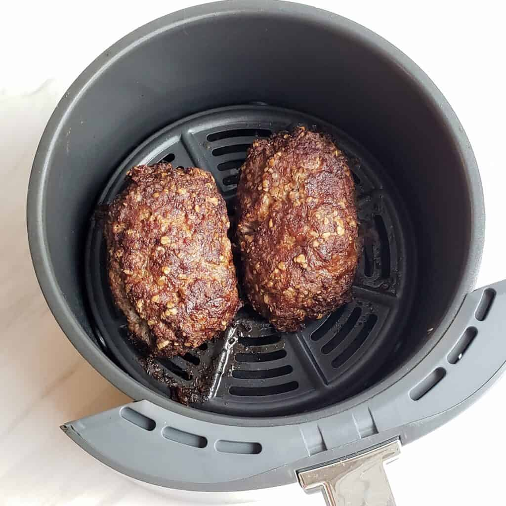 Two cooked meatloaves in an air fryer