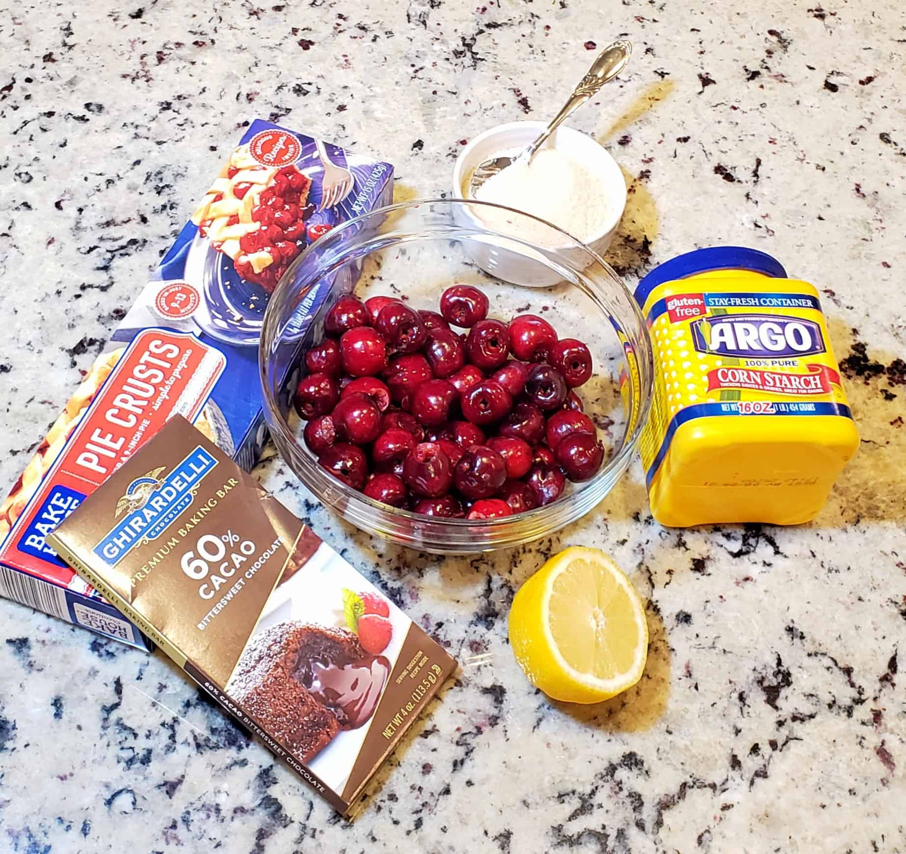 bowl of fresh cherries, lemon, cornstarch, chocolate bar and box of pie crust on a granite surface