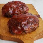 Two small meat loaves on a wooden cutting board with red sauce on top