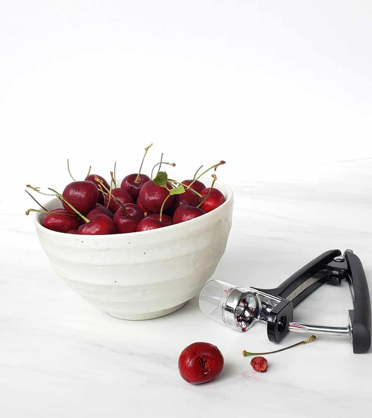 white bowl of bing cherries with stems and cherry pitter