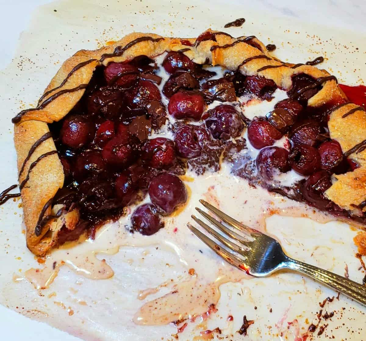 Shortcut Chocolate Cherry Pie  half eaten with melted ice cream and fork on parchment