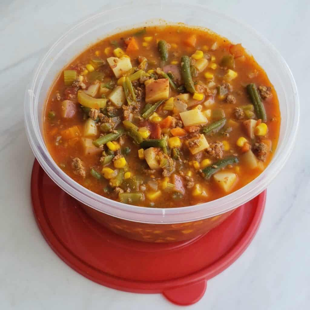 Hamburger Vegetable Soup in a plastic container on a red lid