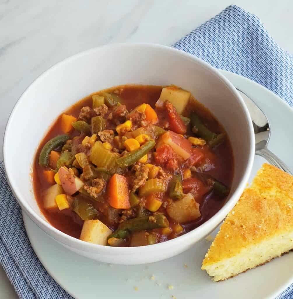 White bowl of hamburger vegetable soup with wedge of cornbread