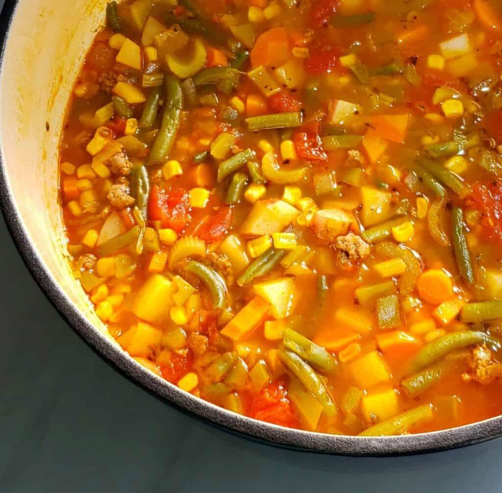 Half of an enamel-coated pot full of vegetable soup