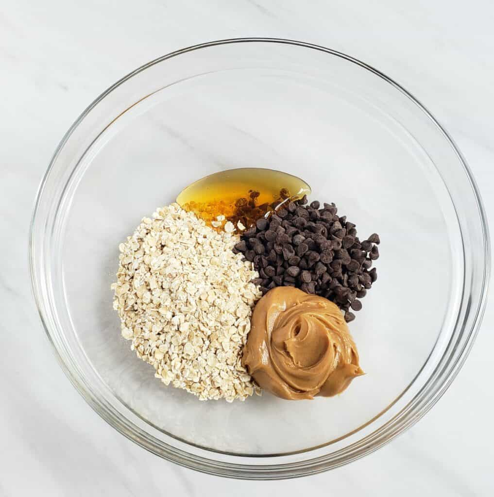 Ingredients: oats, peanut butter, honey, mini chips in a glass bowl