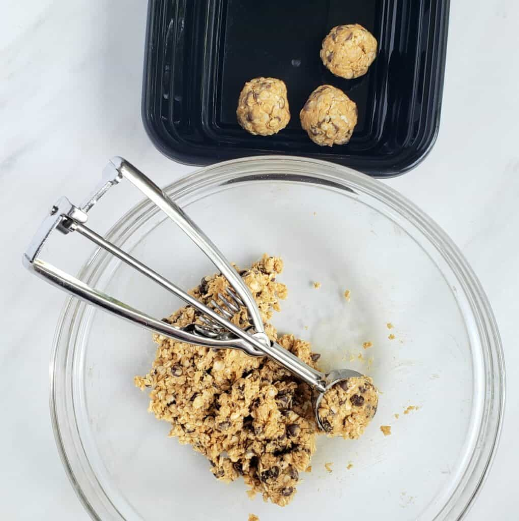small cookie scoop in glass bowl with energy bite dough; rolled balls in black container
