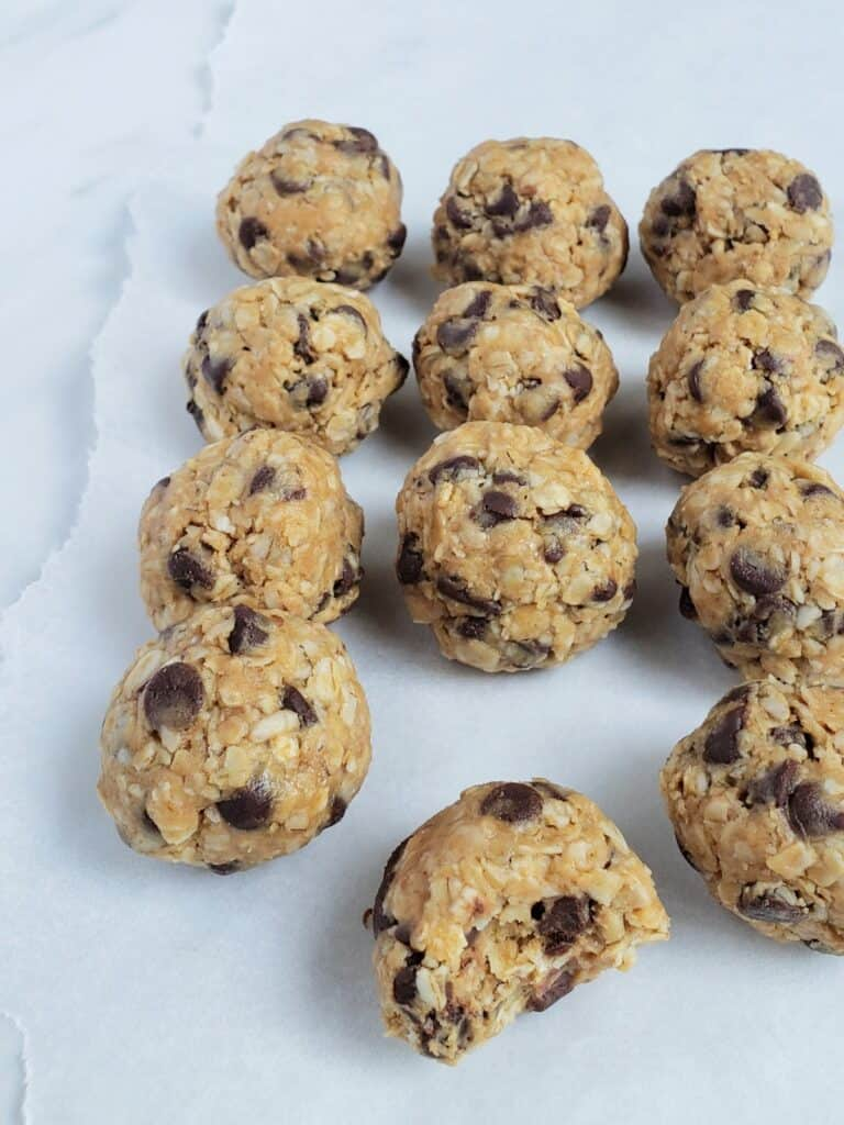 12 peanut butter energy bite balls on parchment paper; bite taken from one