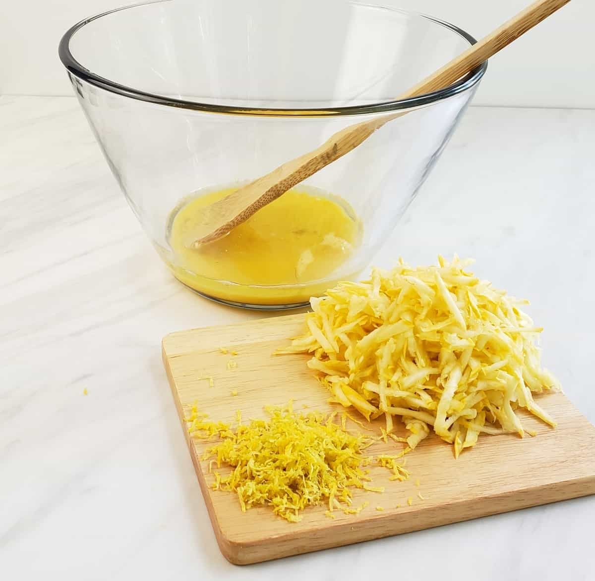Beaten eggs in glass bowl; shredded yellow squash on wooden cutting board