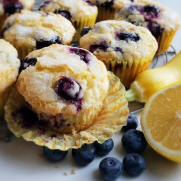 lemon blueberry muffin with paper liner pulled away; blueberries on surface