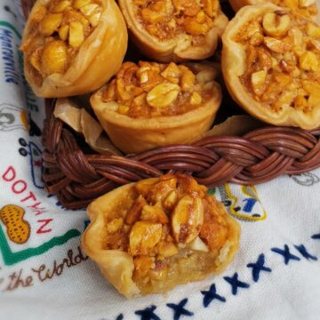 mini peanut pie tassies spilling out from a brown wicker tray onto a cloth with blue x's