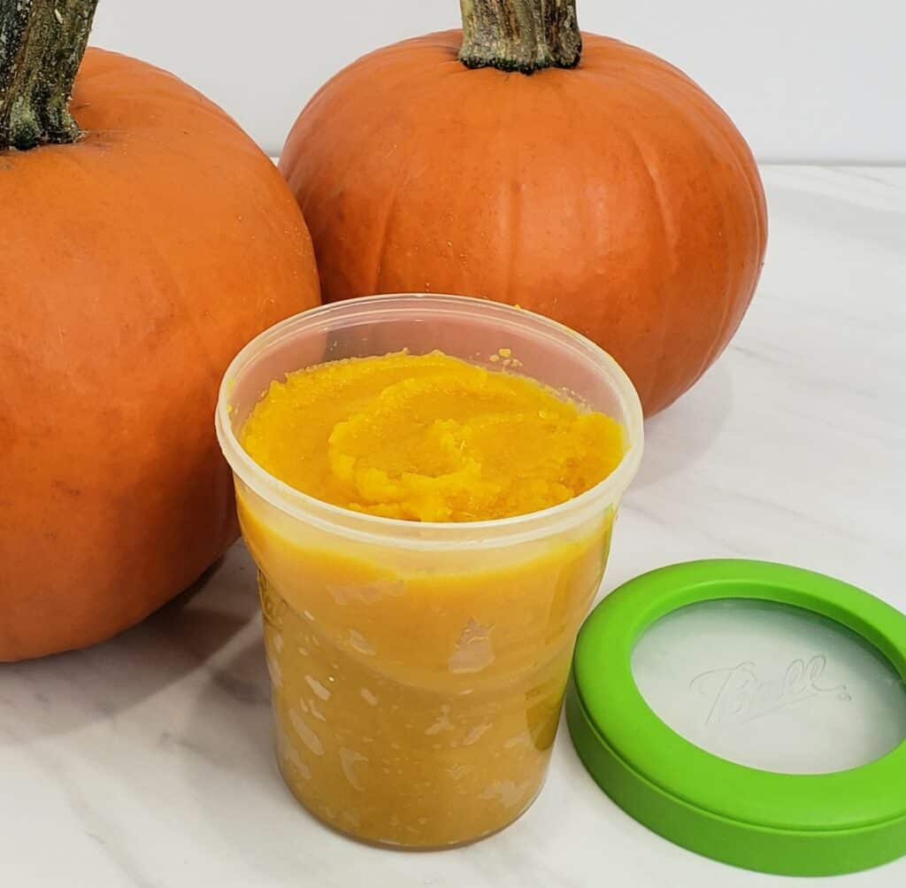pumpkin puree in a freezer container with 2 pumpkins in background