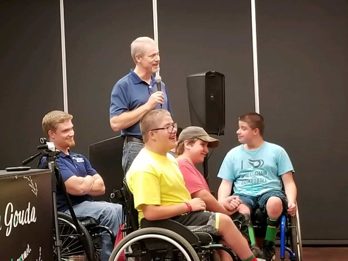 4 boys in wheelchairs, man with mic
