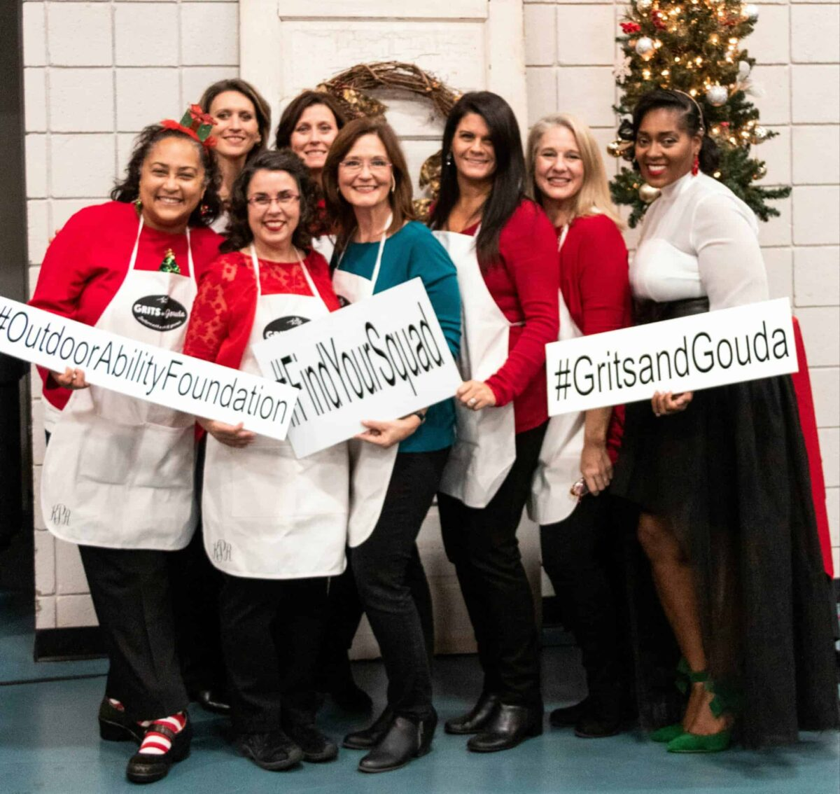8 women wearing white aprons by Christmas tree holding fundraiser signs