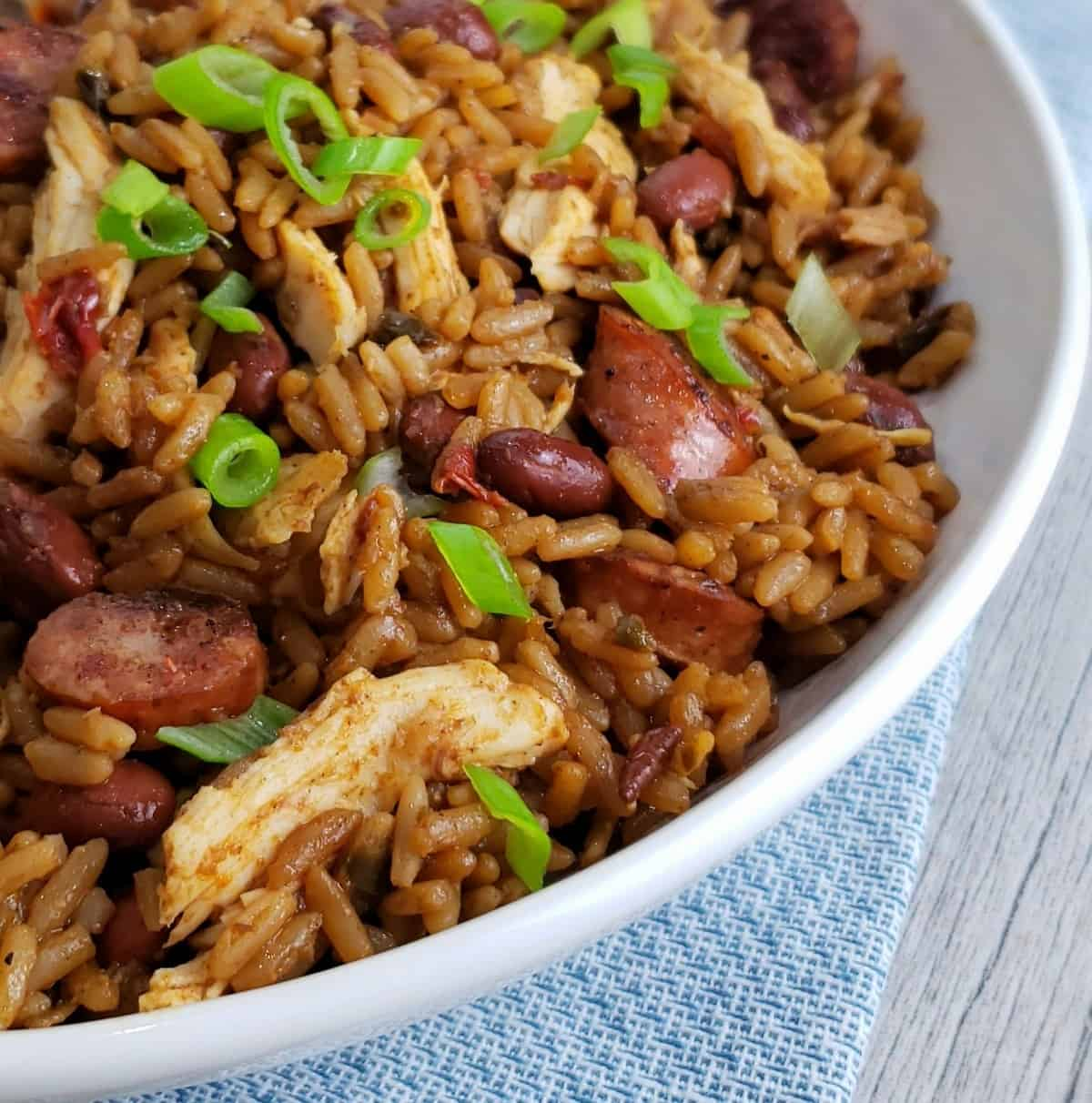 chicken sausage rice red beans green onions in white bowl on blue cloth