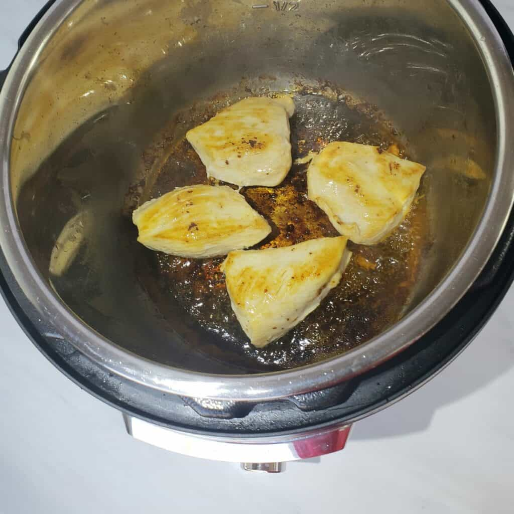 Chicken breasts pieces cooking in an Instant Pot