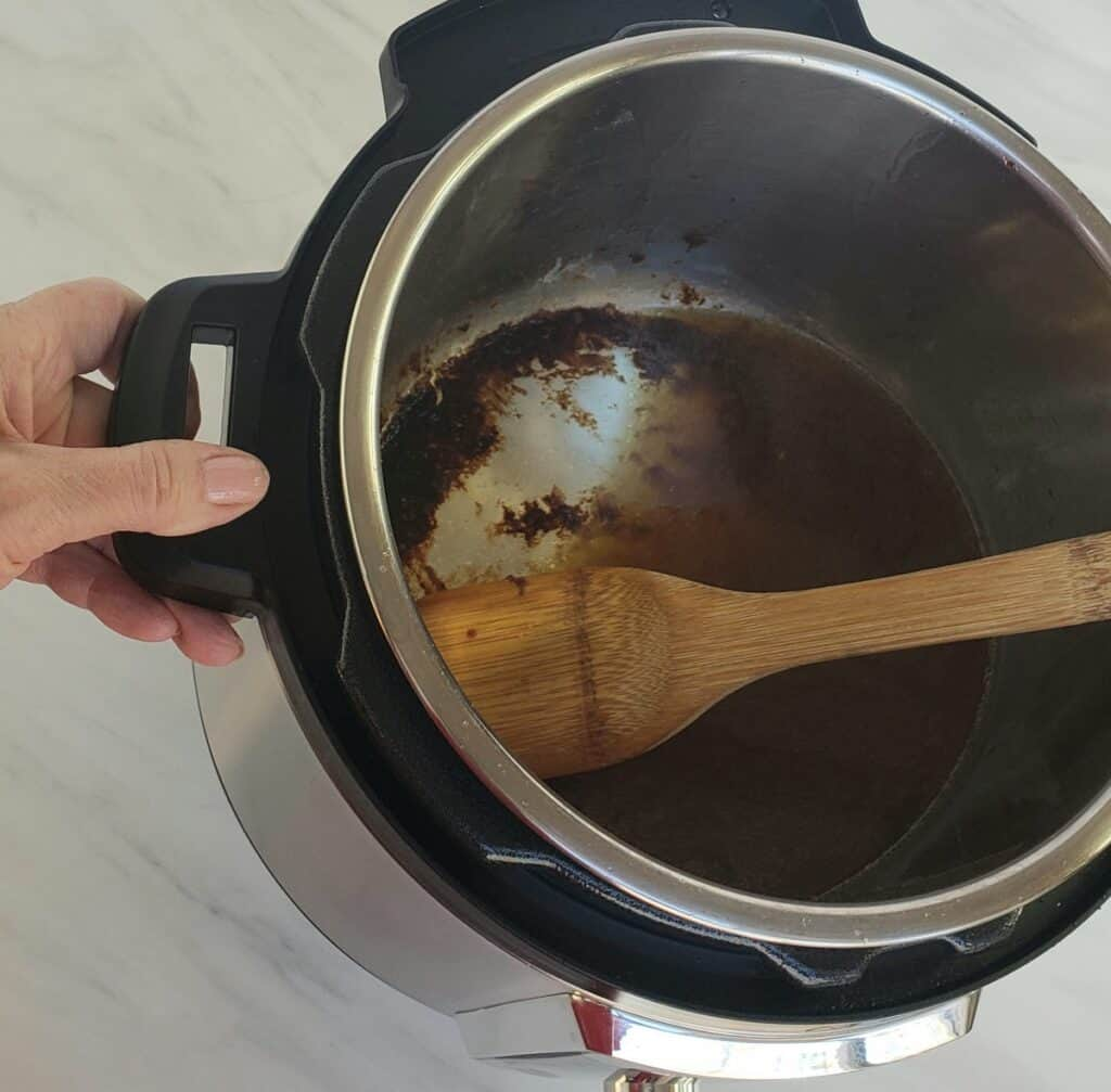 Wood spoon scraping pan drippings from bottom of Instant Pot