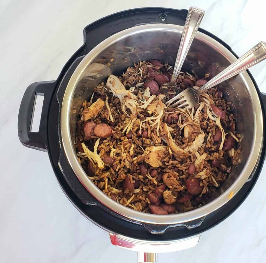 Overhead view of Jambalaya in an Instant Pot with two forks shredding chicken