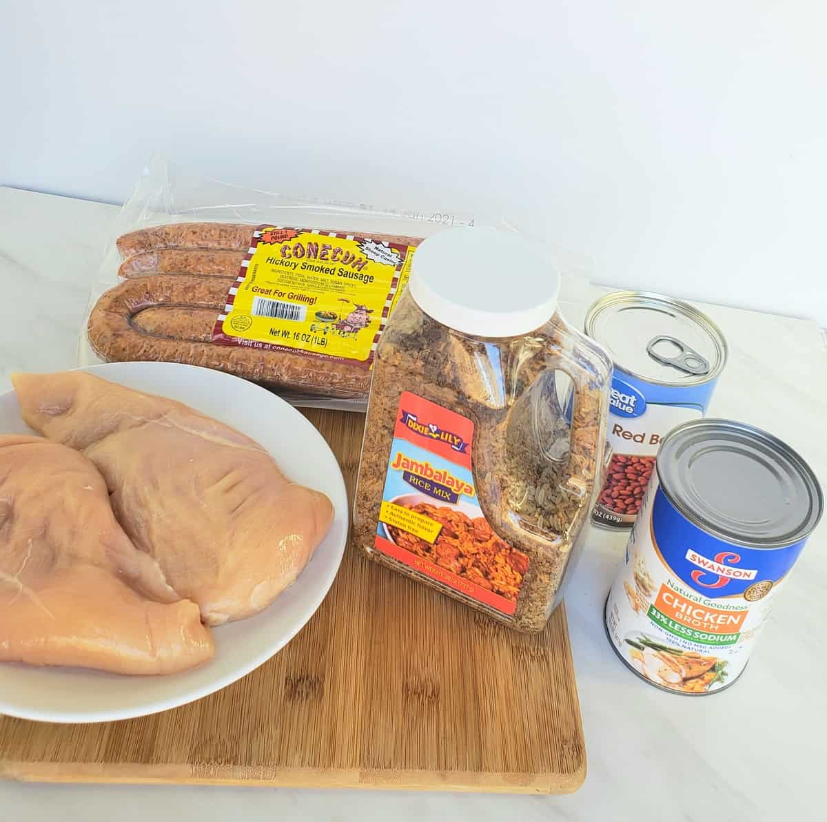 Ingredients: chicken breasts in a bowl, Dixie Lily jambalaya mix, smoked sausage, can of chicken broth, can of red beans