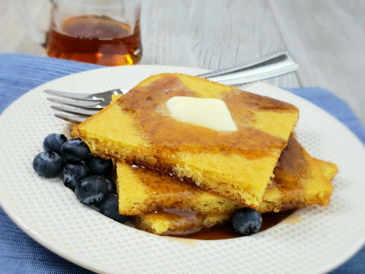 Stack of square pancakes with butter and blueberries on white plate