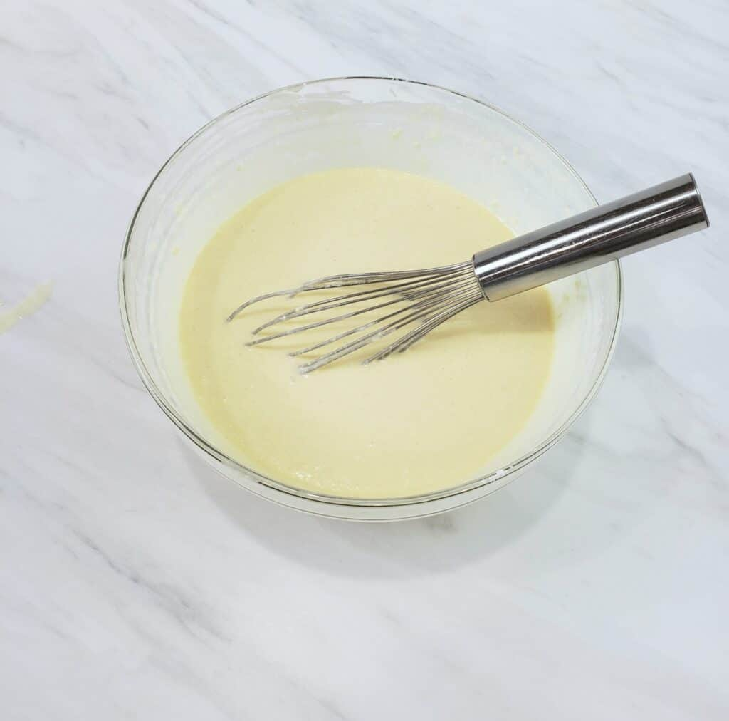 Pancake batter in a glass bowl with wire whisk