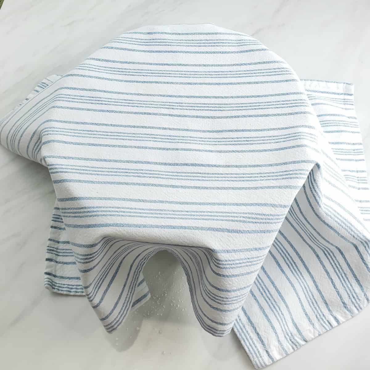 Blue and white towel draped over a bowl on marble surface
