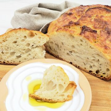 Slice out of artisan round loaf bread. Piece of bread sitting in oil in a plate