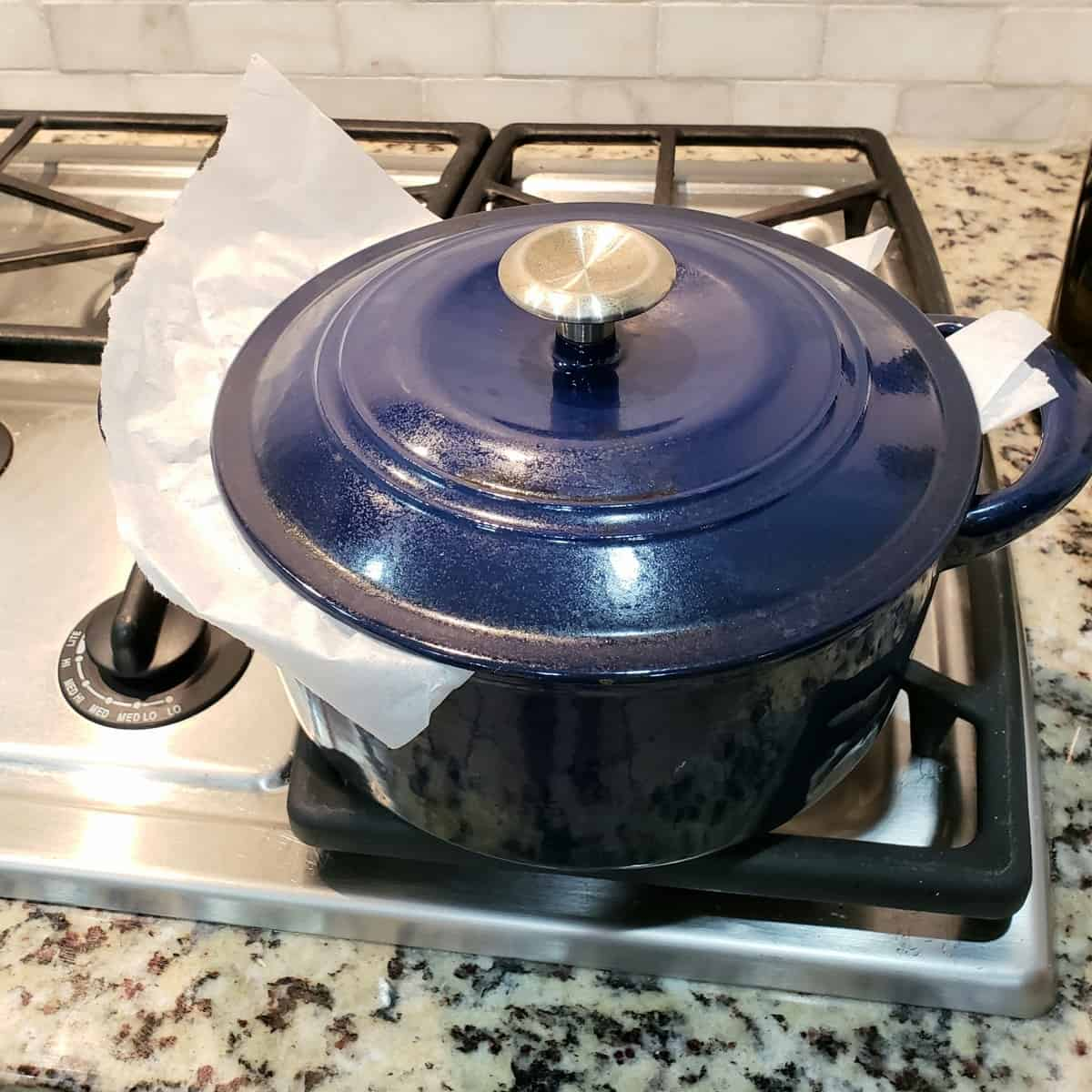 blue cast iron dutch oven on stovetop with parchment sticking out