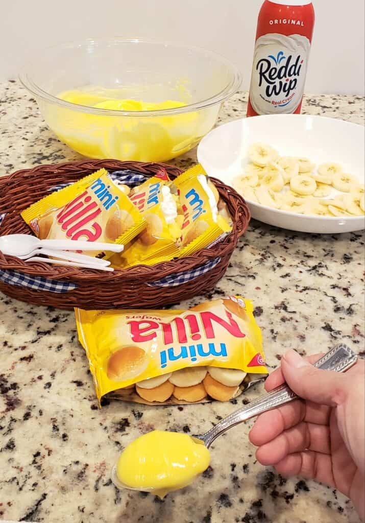 bags of mini vanilla wafers in a brown basket with sliced bananas and a bowl of pudding