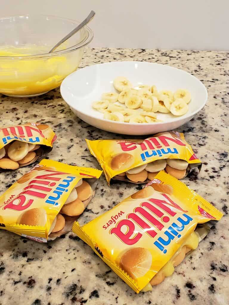 Individual packages of mini vanilla wafer cookies with pudding and sliced bananas in background