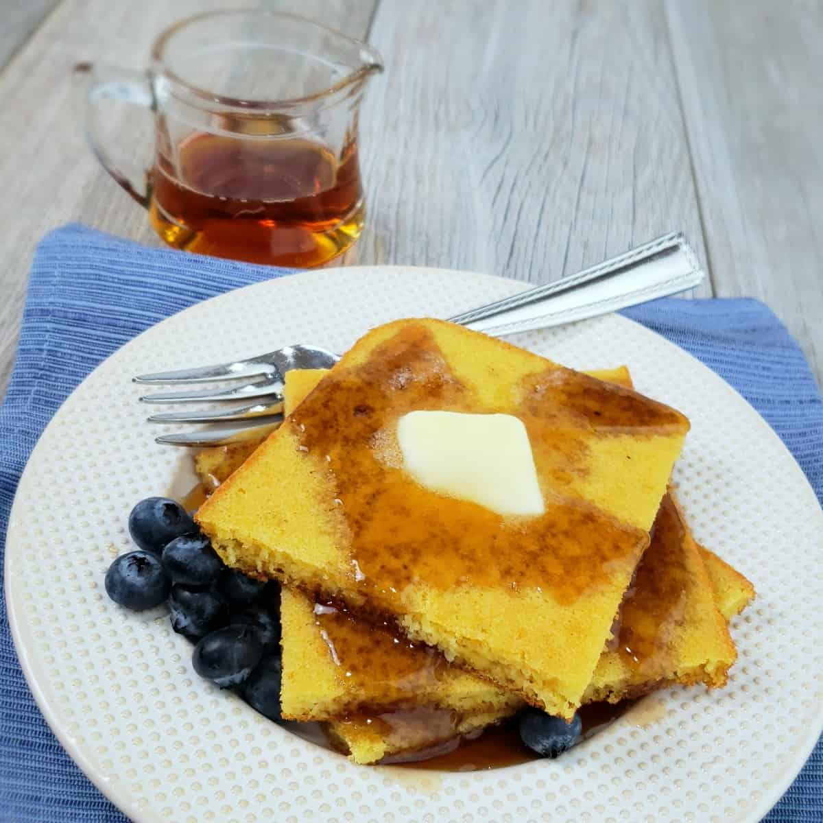 Stack of square pancakes on white plate with butter pat and drizzled syrup; tiny pitcher of syrup in background