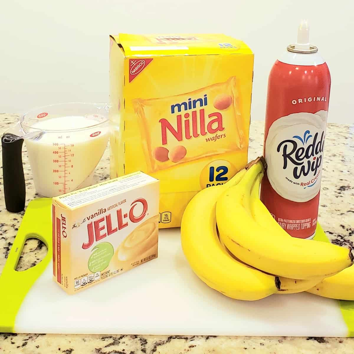 Ingredients on a white cutting board: bananas, Redi whip, Nilla wafers Jello pudding milk