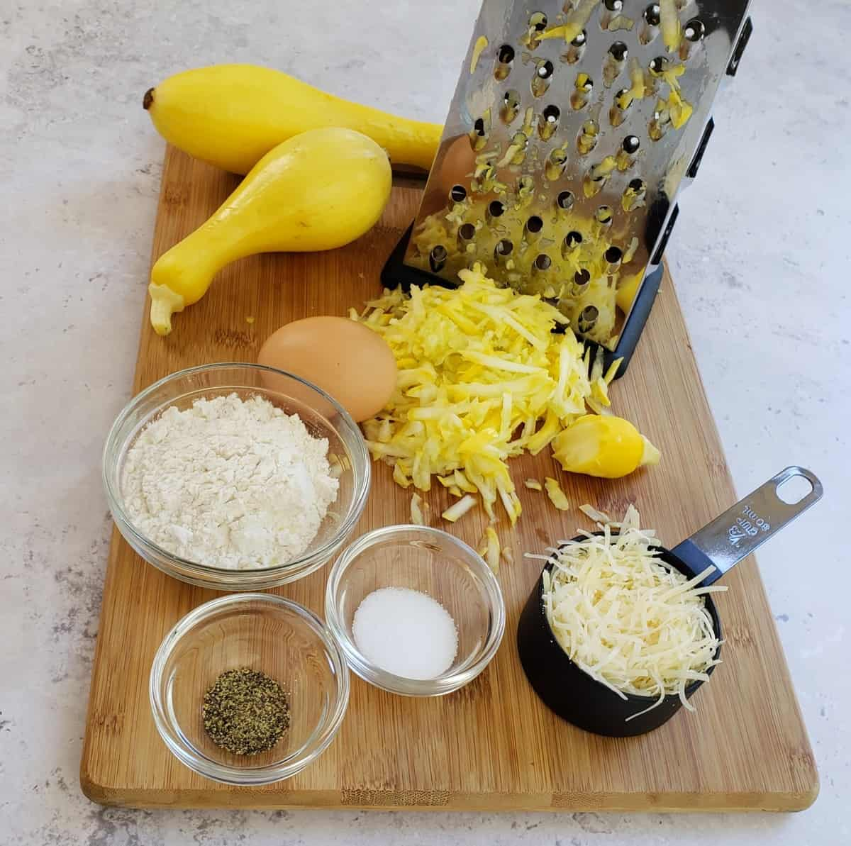 Ingredients on a wooden cutting board: shredded yellow squash, measuring cup of Parmesan cheese, salt, pepper, flour, egg