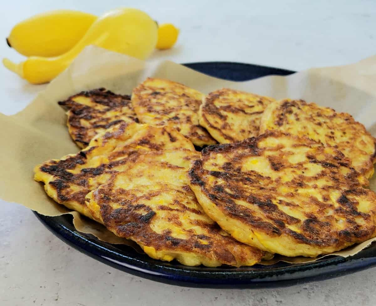 a blue plate of yellow squash fritters with 2 squash in background