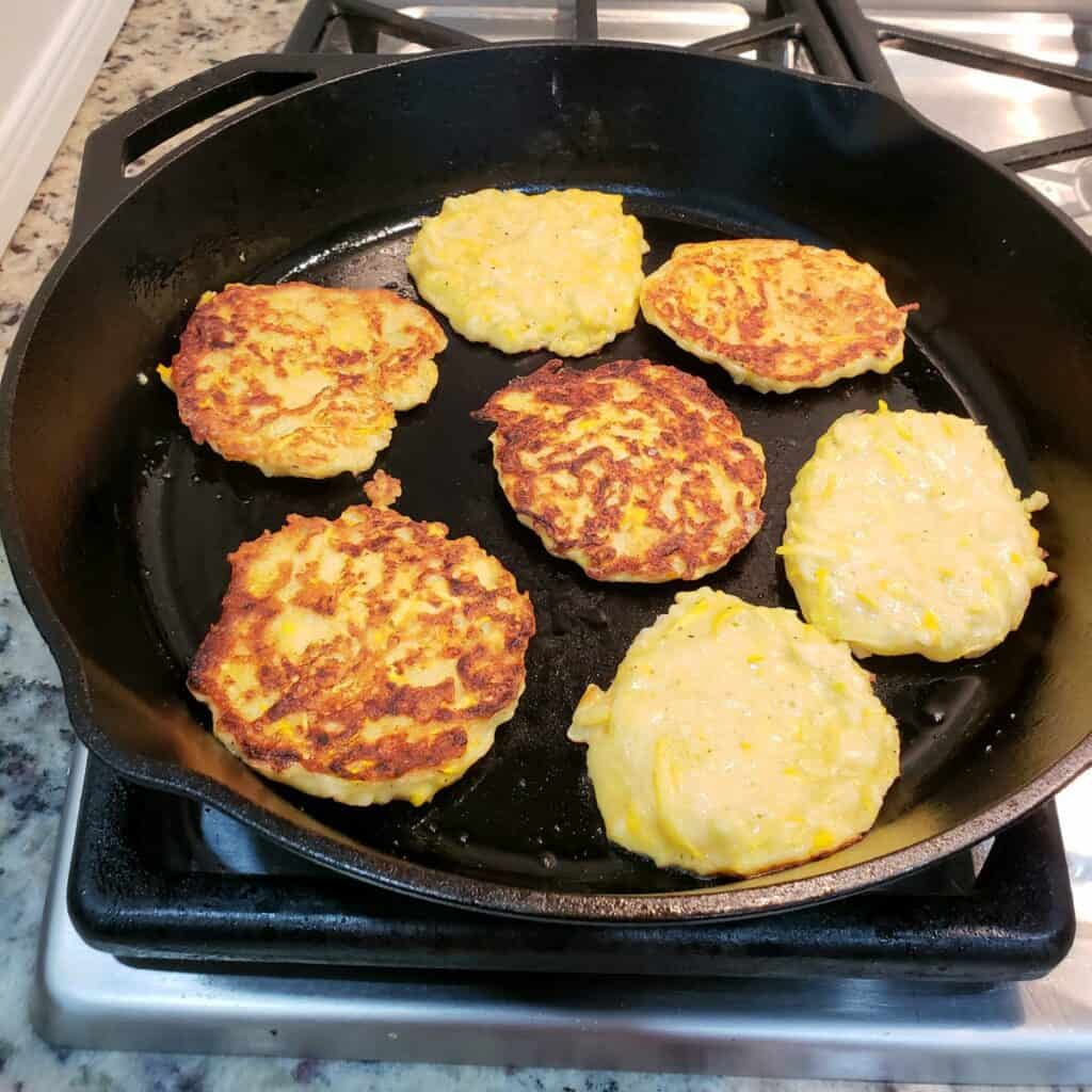 squash fritters frying in a cast iron skillet with some turned over