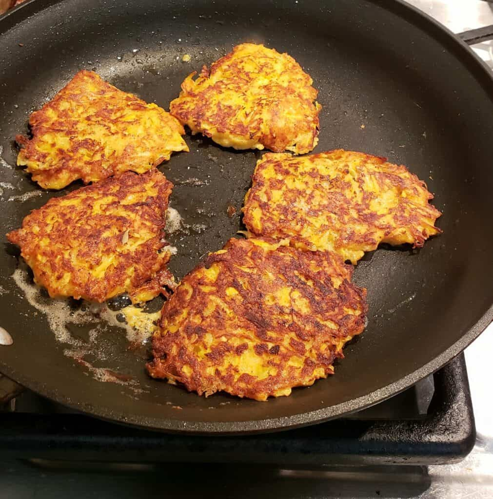 squash fritters frying in a nonstick skillet