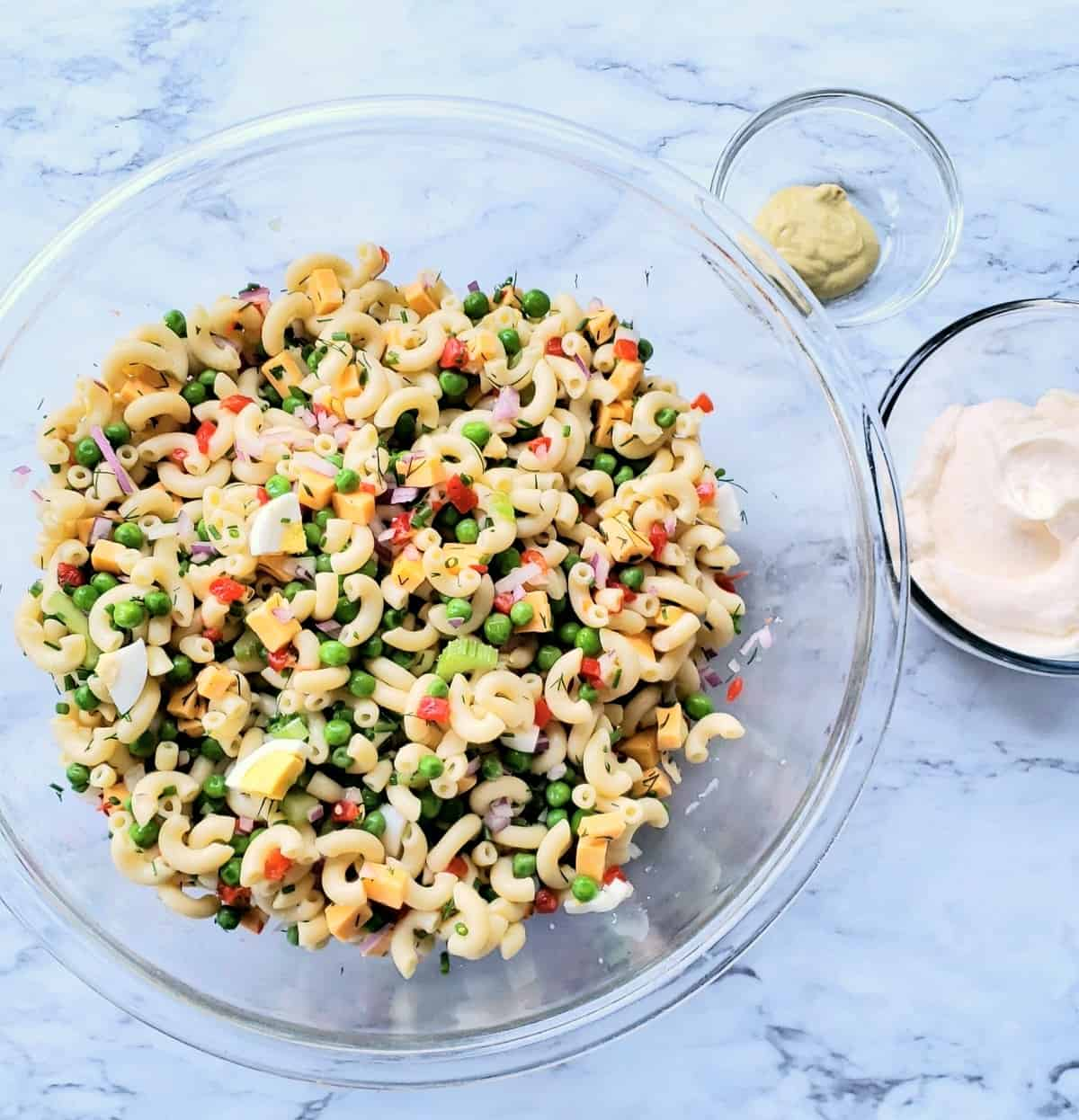 Glass bowl of elbow macaroni salad; two small bowls of mayonnaise and mustard