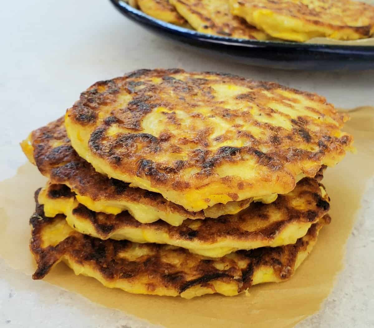 stack of yellow squash fritters with blue plate of fritters in background