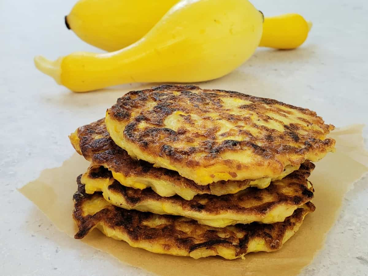 a stack of 4 squash patties with 2 yellow squash in background