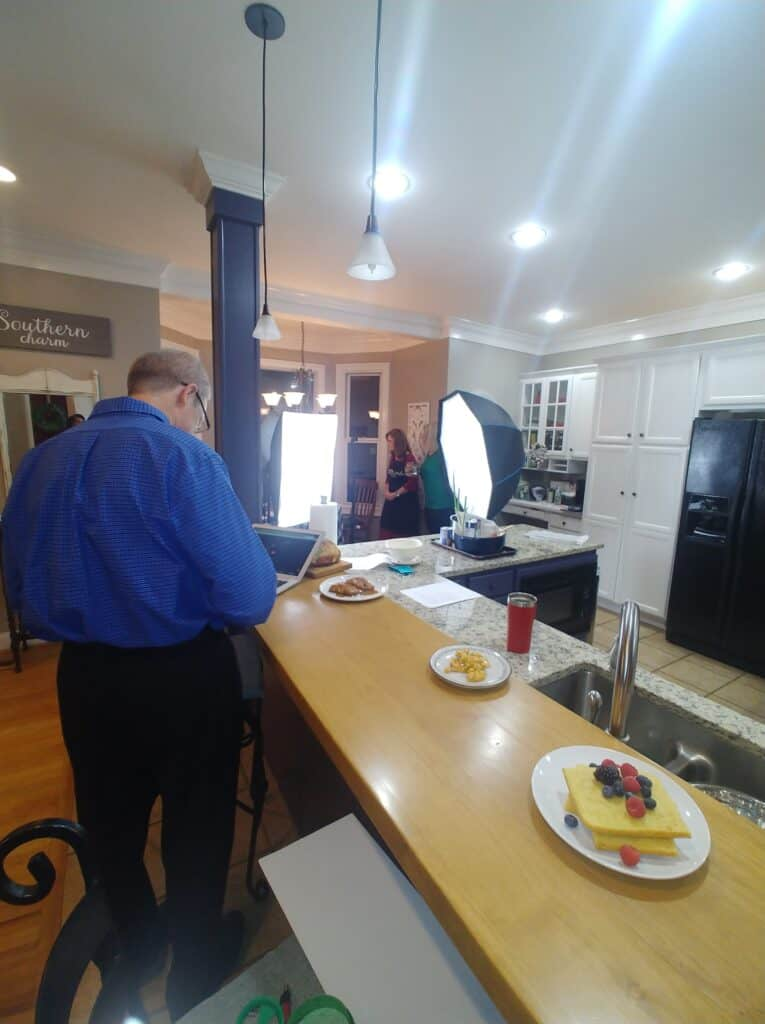 Man with back to camera and studio lights in a kitchen