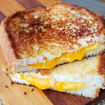 Close up of grilled cheese sandwich sliced in half and stacked on wooden cutting board